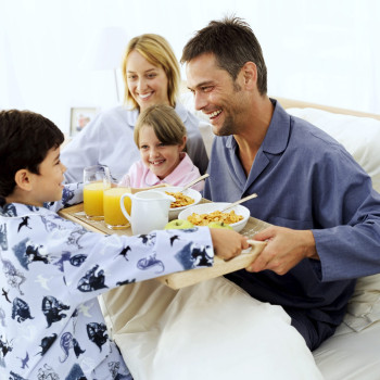 Boy Giving His Parents and Sister (5-9) Breakfast in Bed